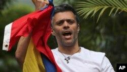 Tokoh oposisi Venezuela Leopoldo Lopez memegang bendera nasional saat menyambut pendukungnya di rumahnya di Caracas, Selasa (1/8).