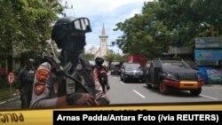 Para polisi bersenjata menjaga sepanjang jalan yang sudah ditutup menyusul ledakan di luar Gereja Katedral di Makassar, Sulawesi Selatan, Minggu, 28 Maret 2021. (Foto: Arnas Padda/Antara Foto via Reuters)
