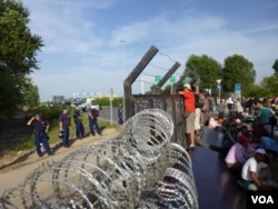 FILE - Refugees and migrants find a border fence of razor wire at the Serbia-Hungary border crossing, Sept. 15, 2015. (Henry Ridgwell/VOA)