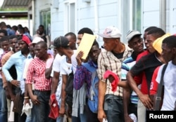 Haitians stand in line as they try to join the country's reformed military in Gressier, Haiti, July 18, 2017.