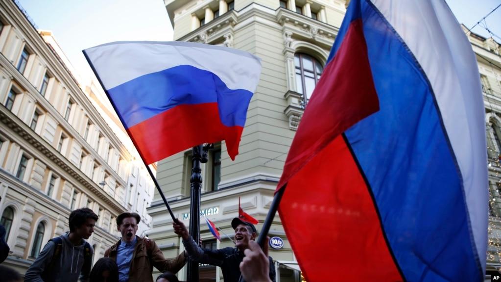 Fans rusos ondean bandeas de su país mientras aficionados de países participantes se reúnen en la calle Nikolskaya en Moscú para celebrar el inicio de la Copa Mundial de Fútbol de la FIFA el miércoles, 13 de junio de 2018.