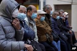 FILE - Elderly men sit at a park wearing face masks in Hong Kong, Jan. 30, 2020.