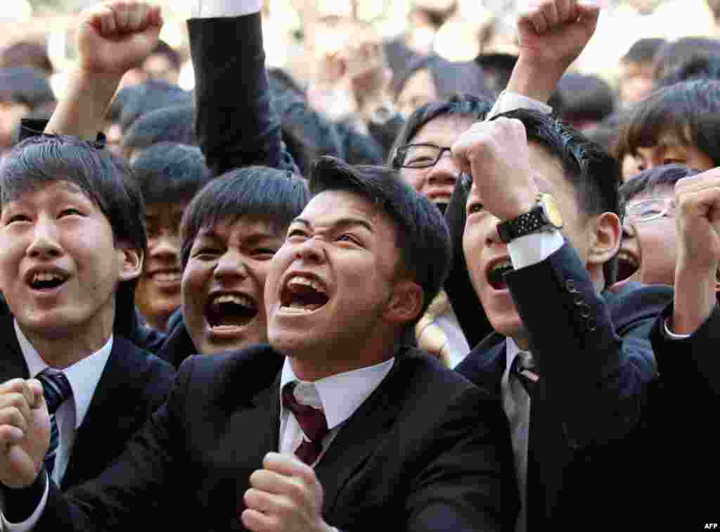 College students raise their fists in the air and yell to kick off a ceremony marking the start of the job-hunting season in Tokyo. Some 1,500 students, who will graduate from schools in March 2016, attended the annual ceremony which aims to encourage future graduates to look for employment.