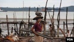 Một phụ nữ đi nhặt gỗ trong khu xóm bị thiêu rụi của người Hồi giáo ở thị trấn Kyauk Phyu trong bang Rakhine ở Miến Ðiện (Ảnh D. Schearf/VOA), tháng 11/2012.