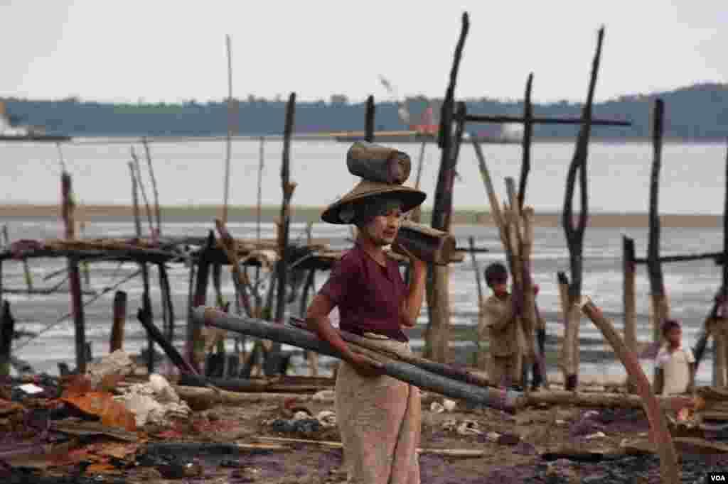 Seorang perempuan mengangkut kayu bakar di perkampungan Muslim yang dibakar di Kyauk Phyu, Rakhine.