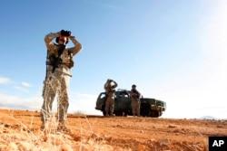 FILE - In this Jan. 19, 2007, photo, a National Guard unit patrols at the U.S.-Mexico border in Sasabe, Arizona.