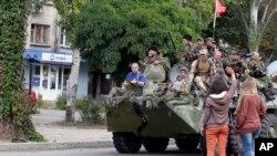 Warga melambai kepada pemberontak pro-Rusia dalam parade di Luhansk, Ukraina timur (foto: dok).