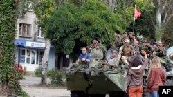 Warga melambai pada pemberontak pro-Rusia di atas kendaraan berlapis baja.