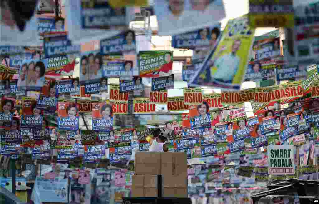 A Filipino worker riding on top of a vehicle dodges campaign posters hanging across the streets of Manila, Philippines. Campaign posters can be seen on almost every corner of the city as the country prepares to vote for a new president and other officials on May 9.