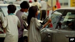 Cambodian child vendors sell newspapers to a car driver at a retail gas station in Phnom Penh, file photo.
