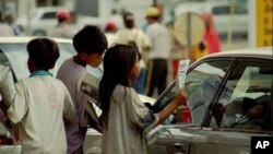 Cambodian child vendors sell newspapers to a car driver at a retail gaz station in Phnom Penh, Cambodia.