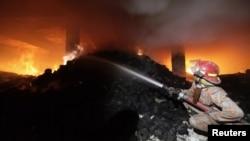 آگ بجھانے والا کارکن آتشزدگی پر قابو پانے کی کوشش میں مصروف