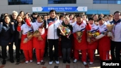Sarah Murray, center, head coach of the combined women's ice hockey team is seen as North Korean women's ice hockey players arrive at the South Korea's national training center, Jan. 25, 2018, in Jincheon, South Korea.