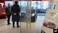 A sales staff chats with a customer at a Tesla store near a poster announcing orders of the Model 3 electric cars in Beijing, China, Monday, Jan. 7, 2019.