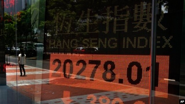 Woman walks past electronic board showing Hong Kong share index, July 3, 2013.