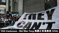 """反暴力遊行隊伍抵達終點香港警察總部,展示大型英文標語""""他們不能把我們殺光"""""""