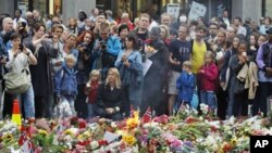 人们在奥斯陆教堂前纪念遇难者的花海前面驻足