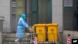 Працівники переміщують контейнери з біологічними відходами біля медичного центру в Ухані