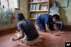 Christian Burmese refugees fix the linoleum floor of their classroom in Kuala Lumpur, Malaysia, March 11, 2017. An Associated Press analysis suggests that the people hurt most by President Donald Trump's planned deep cuts in refugee visas are from Myanmar.