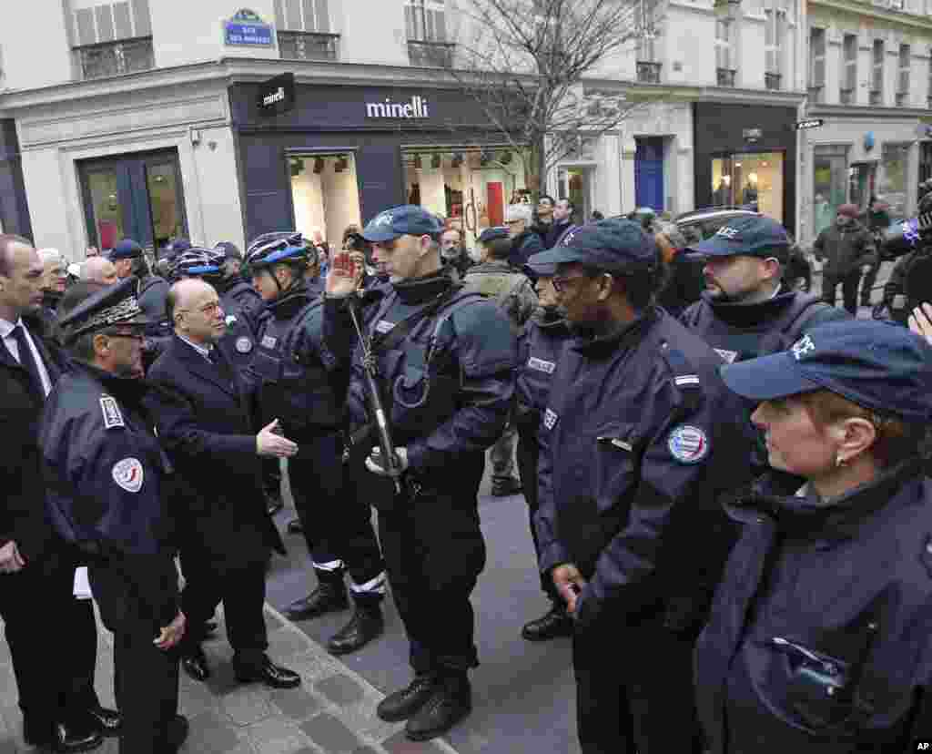 French interior minister Bernard Cazeneuve (third left) meets police officers during a visit to Rue des Rosiers in the heart of the Paris Jewish quarter, Jan. 12, 2015.