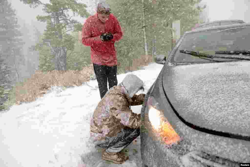 Jacob Ackman từ thành phố Reno, bang Nevada, Mỹ, chờ người bạn Tiger Bortin mắc dây xích vào bánh xe của họ, bên Quốc lộ 88 ở Woodford, California, ngày 24 tháng 11, 2015, trong khi một cơn bão mùa đông ập vào bang bị hạn hán nặng nề.
