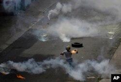 Un manifestante lanza una bomba molotov a la policía que lanzó gases lacrimógenos a una protesta de médicos y estudiantes de medicina que exigían la apertura de un canal humanitario en Caracas.