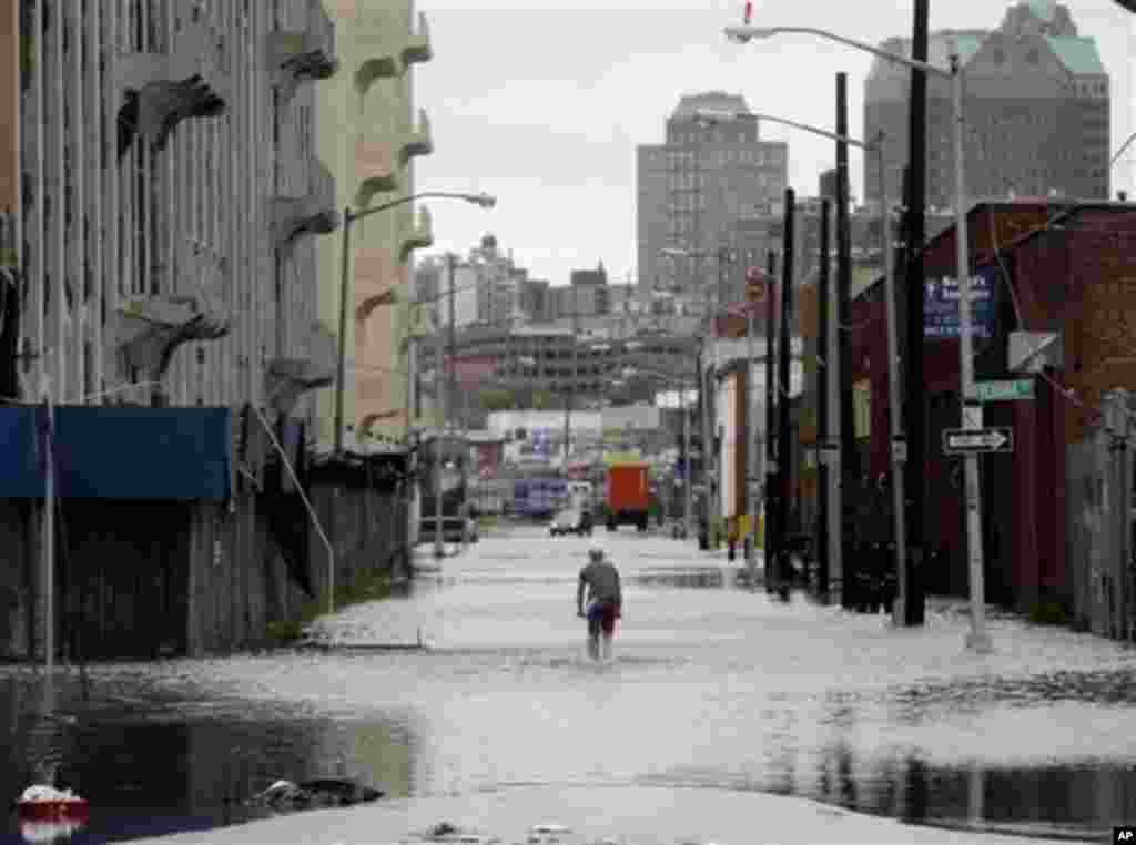 A police officer is parked at the end of a flooded street in Brooklyn, New York, Sunday, Aug. 28, 2011. Seawater surged into the streets of Manhattan on Sunday as Tropical Storm Irene slammed into New York, downgraded from a hurricane but still unleashing