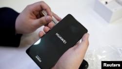 """資料照:北京一名銷售員為顧客啟動華為的P30手機。華為手機被發現把上面原有的時區設定從""""台灣""""變成了""""台灣(中國)""""。"""