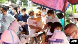 Residents queue to take nucleic acid tests for the coronavirus in Wuhan in China's central Hubei province on August 3, 2021, as the city tests its entire population for Covid-19. (Photo by STR / AFP)