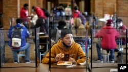 FILE - In this March 31, 2021, file photo, freshman Hugo Bautista eats lunch separated from classmates by plastic dividers at Wyandotte County High School in Kansas City, Kan., on the first day of in-person learning. (AP Photo/Charlie Riedel, File)
