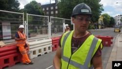ARSIP - Iosif Achim, manajer logistik berusia 32 tahun asal Rumania, kanan, berdiri di lokasi konstruksi sambil melayani wawancara (24/6/2016). London, Inggris. (foto: AP Photo, Pawel Kuczynski)