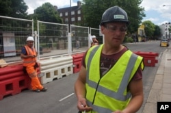 FILE - In this photo taken June 24, 2016, Iosif Achim, a 32-year-old Romanian logistics manager, right, stands at a construction site while being interviewed in London.