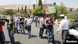 Các nhà báo chờ đợi tại Quảng trường al-Rawda, gần 1 con đường dẫn đến tòa nhà an ninh quốc gia, sau khi lối vào khu vực này bị chặn tại Damascus, 18/7/2012