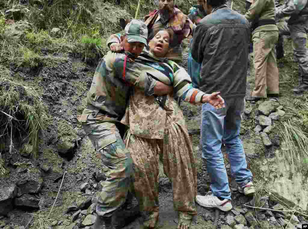 An Indian soldier carries a stranded woman pilgrim to a safer area in Chamoli district, in the northern Indian state of Uttarakhand, June 18, 2013.