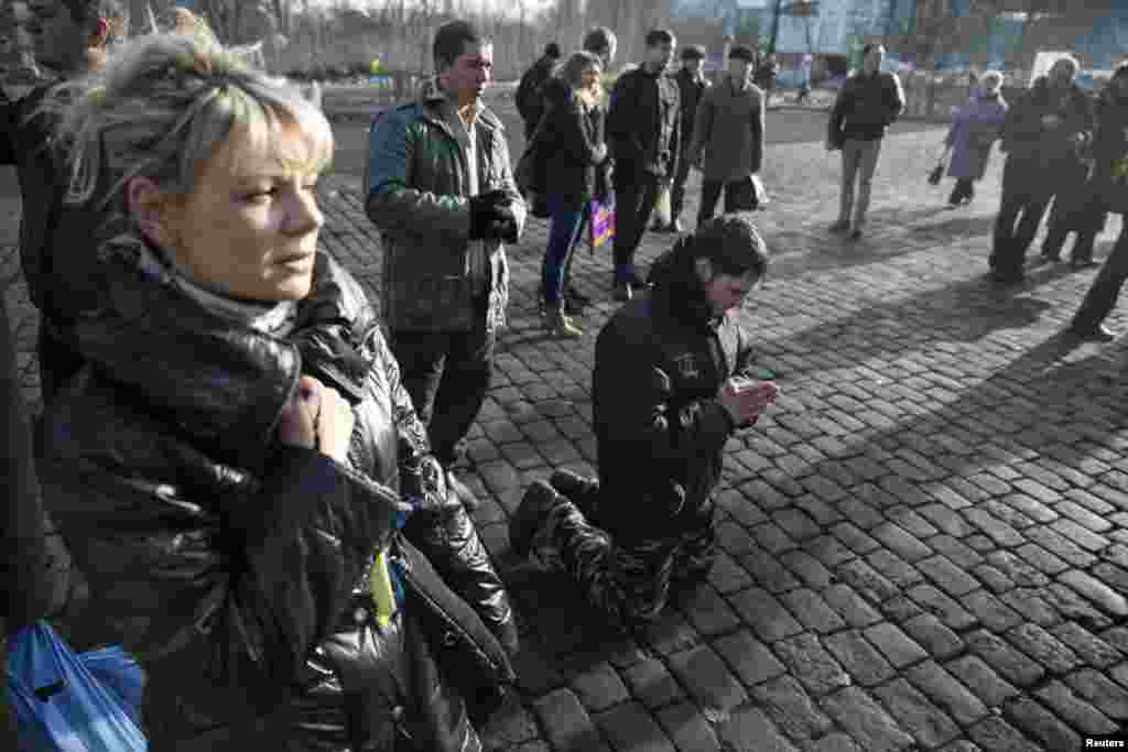 A man kneels as he pays his respects to fallen anti-Yanukovych protesters near Kyiv's Independence Square, Feb. 24, 2014.