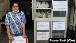 Pendeta Forida Rambu di samping lemari makanan yang disediakan bagi para pekerja harian lepas. (Foto: VOA/Petrus Riski)