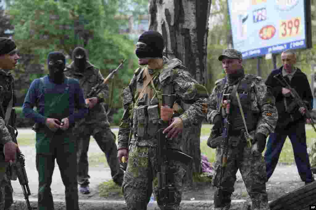 Pro-Russian gunmen listen to instructions from their commander (center) behind barricades in Slovyansk, May 2, 2014.