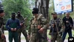 FILE - Pro-Russian gunmen listen to instructions from their commander, center, behind barricades in Slovyansk, eastern Ukraine, Friday, May 2, 2014.