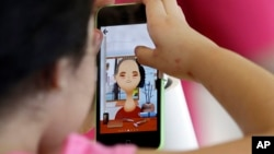 FILE - A young girl plays a game on the new iPhone5c.
