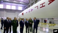FILE - Russian Prime Minister Dmitry Medvedev (3rd-R) visits an assembly shop, with Angara booster rocket at right, at the Plesetsk Cosmodrome in Plesetsk, northwestern Russia.