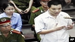 """FILE - Nguyen Van Dai, right, testifies in this May 2013 file photo, originally taken from TV footage. The well-known Vietnamese human rights lawyer was arrested Wednesday on anti-state """"propaganda"""" charges."""