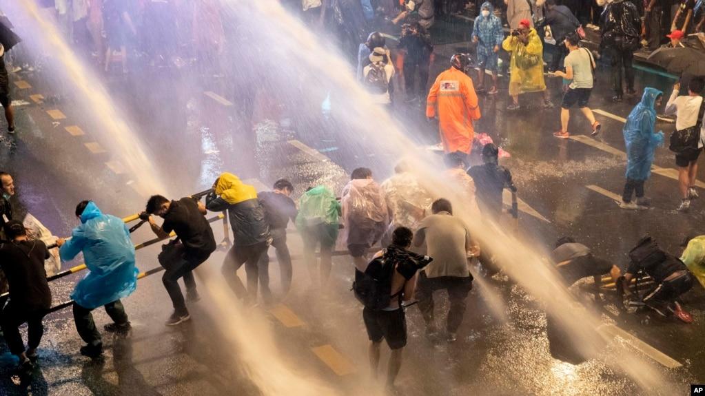在泰国首都曼谷,警察们试图用水枪驱散抗议者们。(2020年10月16日)