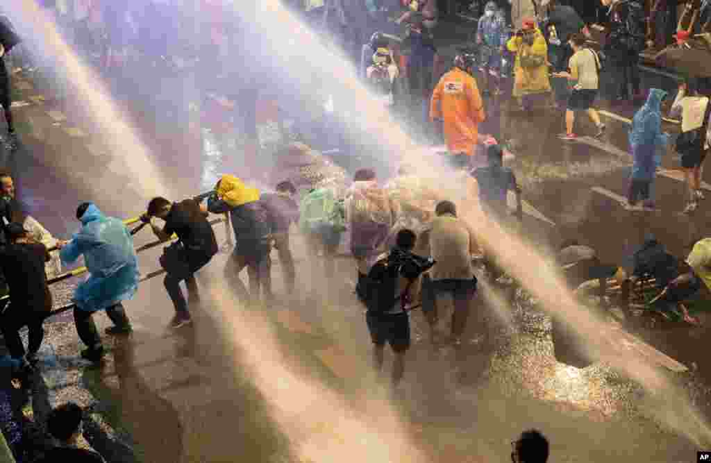 Pro democracy demonstrators face water canons as police try to disperse them from their protest venue in Bangkok, Thailand, Friday, Oct. 16, 2020. Thailand prime minister has rejected calls for his resignation as his government steps up efforts to stop st
