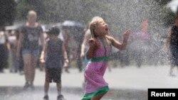 Seorang gadis cilik berlari di tengah percikan air dari selang di depan sebuah memorial di Washington, D.C., saat temperatur di ibukota mencapai lebih dari 38 derajat Celcius (foto: dok).