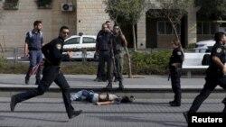 Sarkaal booliis Israeli ah oo ag taagan meydka qof Falastiini ah oo ay toogteen, markii uu weerarka minidida qaaday kadib.