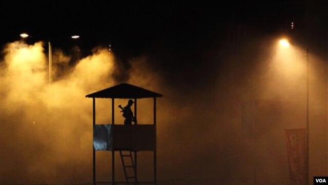 Seorang aparat keamanan terlihat berjaga-jaga di menara saat berlangsung penyemprotan anti-nyamuk di gedung yang akan dipakai untuk Pesta Plahraga Persemakmuran.