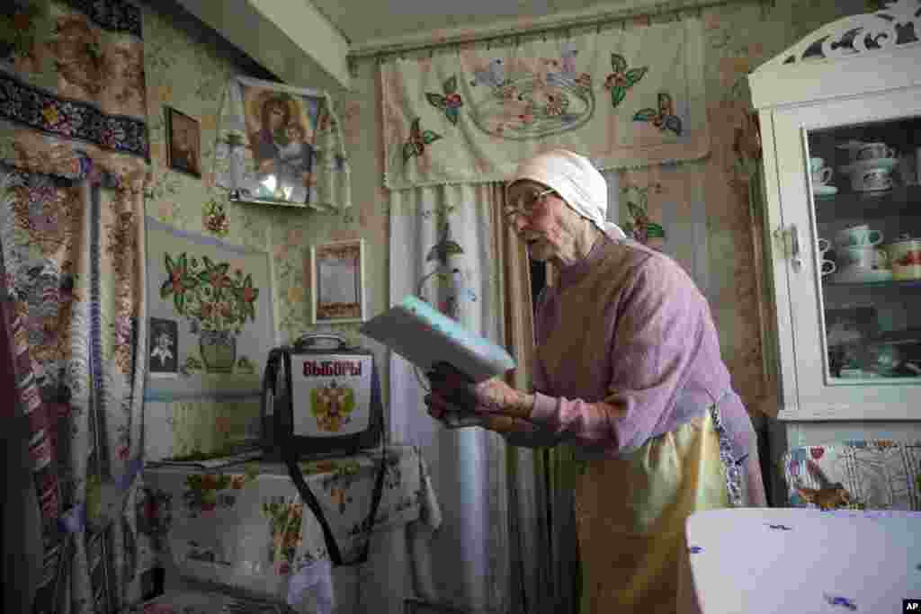 Galina Shalygina, 85, prepares to cast her ballot in a ballot box brought by election officials to villagers unable to travel to the polling station, in the village of Seltso, near Kostroma, 350 km (218 miles) northeast of Moscow, Russia. Voters are casting ballots across the country for local legislators and governors, in elections expected to be won by candidates loyal to President Vladimir Putin.