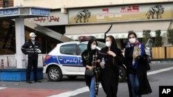 2020年2月23日,在伊朗首都德黑蘭市中心商業區,警察和行人都戴著口罩。