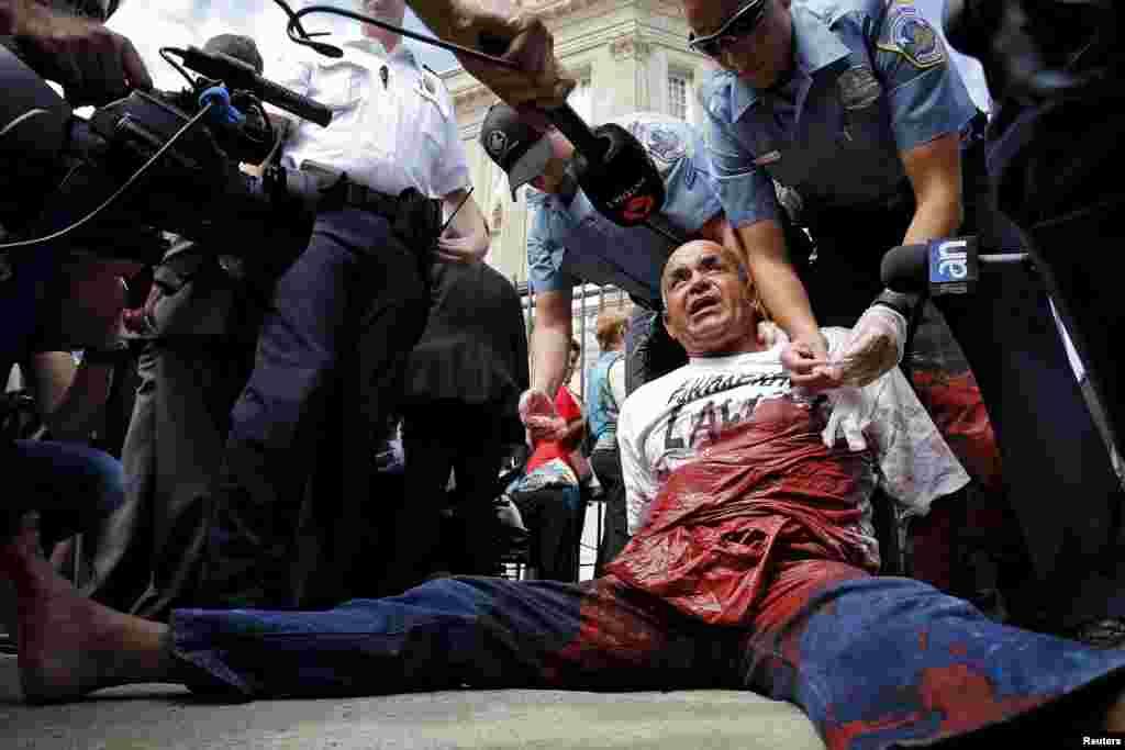Cảnh sát bắt giữ Danilo Maldonado, một người biểu tình, sau khi ông ta vấy sơn đỏ từ một túi giấu trong quần áo của ông ta, bên ngoài buổi lễ thượng kỳ tại Đại sứ quán Cuba ở Washington, Mỹ.