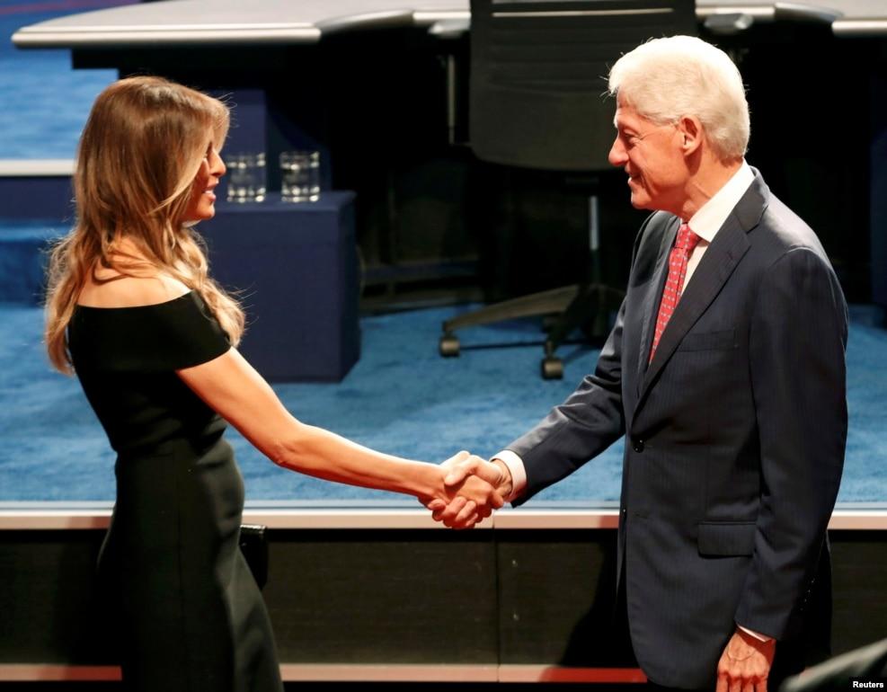 """2016年9月26日,在總統候選人第一次辯論的場所,克林頓前總統和川普夫人握手。 當時這兩人都在爭取讓自己的配偶成為下一任總統,自己成為""""第一配偶"""""""